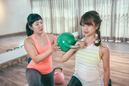 professional Asian fitness trainer teaching correcting the pose of kettlebells exercise. young coach helping learner doing kettle bells lifting in the gym. sporty woman training arms indoor.