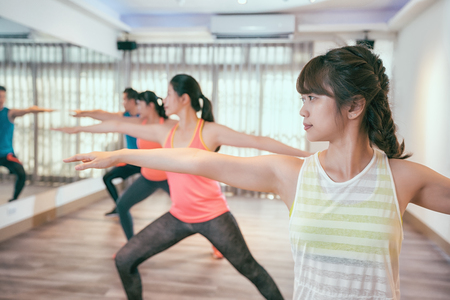 group of adults attending a yoga class indoor in gym. young sporty people doing a warrior pose facing the mirror in classroom at a health club. friends practicing pose together carefree opening arms. Archivio Fotografico