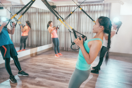young people are training indoors with TRX pulling hard full of power. asian students in gym training arms stronger chest. group of happy friends working out together with straps.