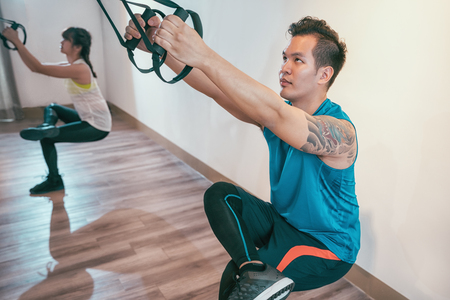 asian handsome man and her girlfriend join sports club trx lesson working out in gym. young muscular couple concentrated doing total body resistance exercises indoor. male in sportswear and tattoo.