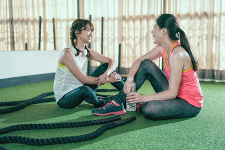 female athletes sitting chatting resting while taking a break after battle rope training lesson. tired sweat women drinking bottle water health love sports. two friends cheerfully laughing in gym.
