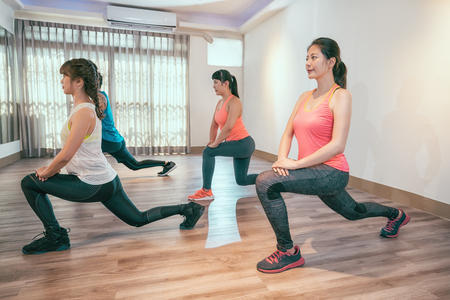 fitness sport training lifestyle concept. group of smiling women stretching in yoga class in gym. young asian people working out indoor at a health club. Stockfoto