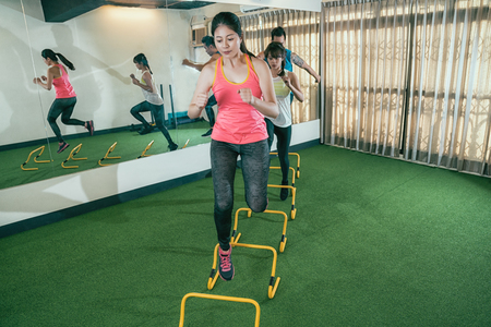 Sportswomen practicing hurdles in gym. group of asian leaner workout for running race in the sport club. sporty athlete people doing exercise training.