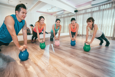 group of asian women and men exercising with kettlebells doing pushups exercise in gym. young people stronger arms muscles by kettle bell exercise. Fitness class and girls and boy training by weights
