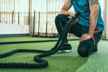 unrecognized man with tattoo kneeling down resting after training with battle rope. asian sporty male trainer tidy up the classroom in gym after a battling ropes lesson. athlete stronger arms muscle.