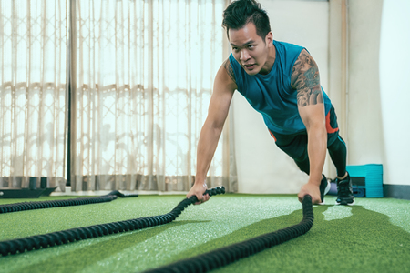 Man with battle rope exercise in the fitness gym. male wearing sportswear doing push ups with battling ropes in CrossFit club. young asian training arms muscles indoor. Stok Fotoğraf - 113314827