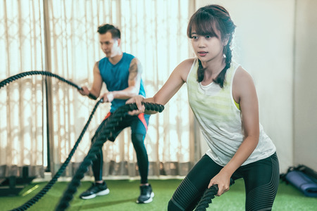 asian athletes doing battle rope workout in sport club. Gym fitness sport fit couple working out battling ropes exercise banner panorama. Woman and man cross training arms muscles. Stock Photo