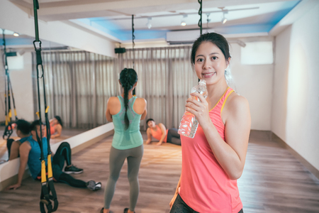 Fitness woman drinking water from bottle. Muscular young female at gym taking a break from workout. group of tired friends sweating resting in the background after trx lesson at health club.