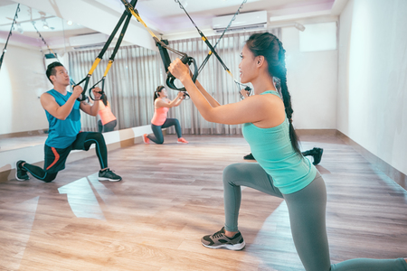 Group of young people are training indoors with TRX. Total Body Resistance Exercises lesson at sport club. asian women and man are working out in gym.