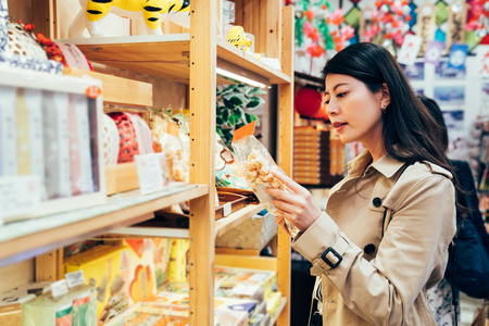 young japanese mom choosing snack for kids in local specialty shop in dotonbori osaka japan. asian mother buying food cookies for family after work in the vendor. beautiful lady reading the mark. Archivio Fotografico