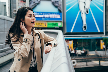 female office worker in downtown business district in osaka japan. young girl relying looking the view in dotonbori cheerfully relaxing. businesswoman standing beside the famous running man sign.