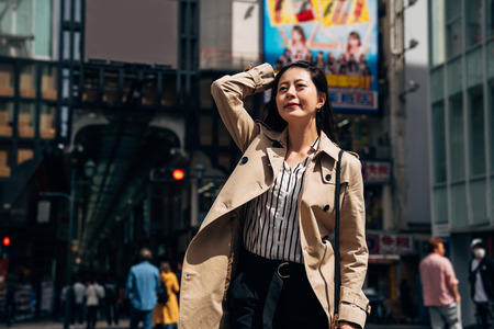 Business woman walking flicks hair. Lawyer professional walking outdoors happy looking at the sunlight smiling on face. young asian office lady joyful waiting traffic light in busy street in japan.