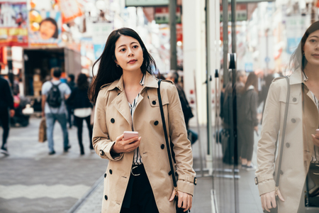 office lady window shopping on summer sale on busy street in dotonbori osaka japan. young girl holding cellphone while walking on the road. modern businesswoman urban city lifestyle concept. Stock Photo