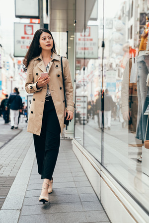 full length of office lady shopping on boxing day after work. young businesswoman wearing smart casual suit walking on the street holding smartphone using texting message. elegant lady in high heels. Stock Photo