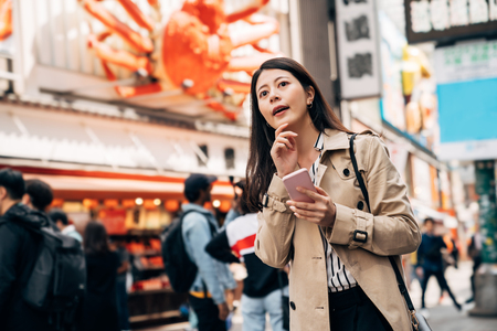 elegant Asian girl using phone checking the right direction finding hotel while having business trip in japan. young lady holding cellphone using online map app dotonbori osaka on sunny day outdoor