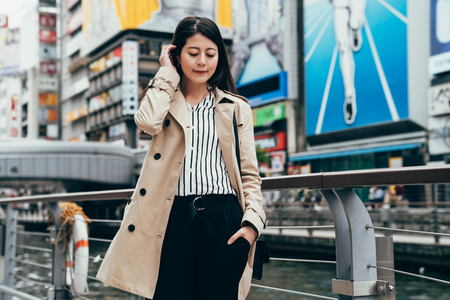 female business worker looking down the ground near the river. beautiful office lady smiling waiting for someone in dotonbori standing near the famous nippon running man sign tourism attraction osaka Stock Photo
