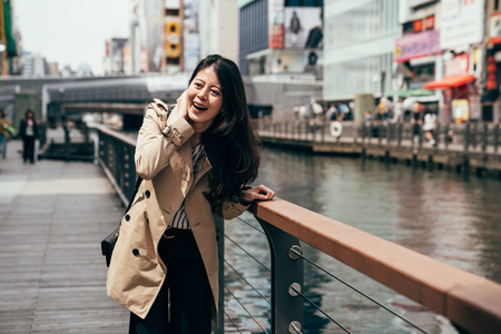 tourist girl laughing relying on the handrail near the river in dotonbori osaka japan on sunny day. young local japanese woman cheerfully having fun beside the canal in popular shopping area.
