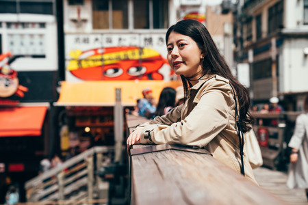 asian woman relying on wooden handrail on the bridge sightseeing down the river. young lady standing above the canal in dotonbori in osaka japan. popular teeming shopping area on sunny day. Stock Photo