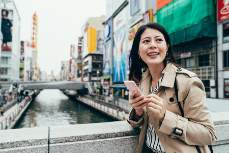 Urban city modern Asian girl using phone app smiling walking on bridge cross the canal in dotonbori osaka japan. Happy young adult business travel trip lifestyle concept in spring with smart casual.