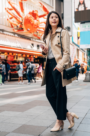 full length of elegant Asian girl using phone checking the right direction to visit customer office. young female super sales finding location of the client's company on dotonbori street food area. Stock Photo