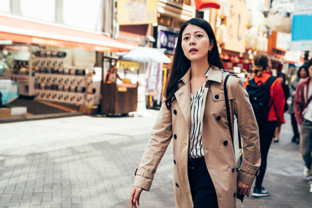 beautiful woman in casual suit walking in dotonbori in osaka city japan. busy urban people lifestyle concept. young girl shopping alone outdoor on sunny day in summer business travel trip. Stock Photo