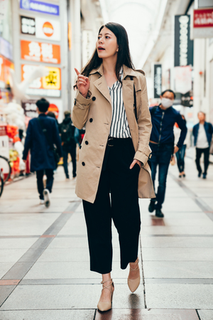 Happy beautiful woman in smart casual suit walking joyful and cheerful smiling pointing finger in shinsaibashi osaka. Pretty sexy fashion model girl in her 20s traveling in japan for business trip Stock Photo