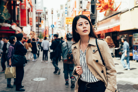 beautiful lady traveler thinking the right way back to hotel after having lunch in dotonbori in osaka japan on sunny day. young asian woman finding the direction standing on the busy urban street.