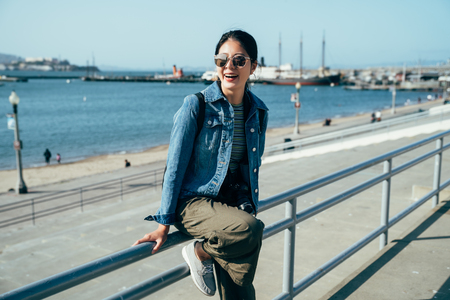 happy girl photographer wearing sunglasses enjoy the beautiful view of blue ocean and sky relying sitting on handrail near the port. young asian woman smiling laughing sightseeing in the pier 39.