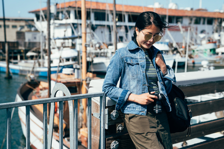 lady photographer holding camera looking at the photography photo standing on the port with ship boats moored in the background. young asian woman zooming up the picture in digicam wearing sunglasses