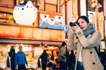 woman photographer visiting busy urban in osaka japan. girl tourist zooming up focus the night city view by slr camera. huge puffer fish balloon hanging in background. Stok Fotoğraf