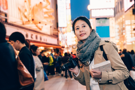 girl tourist smiling holding camera and guidebook standing on the street in dotonbori in osaka japan at night with dark sky in background. busy teeming japanese urban city lifestyle concept.