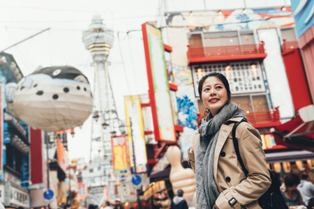 young female traveler cheerfully sightseeing standing on the teeming street in tsutenkaku on sunny day wearing scarf. huge puffer fish balloon flying in the sky. girl smiling looking around on road. Stockfoto