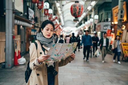 aziatische vrouwelijke toerist die de kaart van de toerismestad vasthoudt in de stad osaka, japan die 's ochtends op de krioelende markt loopt. enorme rode lantaarns die binnenshuis op het dak in het winkelgebied hangen.