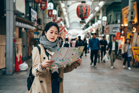 asian female tourist holding tourism city map in osaka city japan walking in the teeming market in the morning. huge red lanterns hanging on the roof indoors in shopping area.