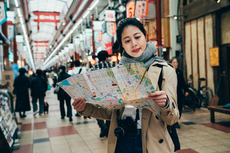 asian tourist cheerfully looking the travel map standing indoors in the market in osaka japan. local japanese people buying shopping for grocery in the morning. young girl finding next plan route