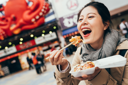cheerful lady tourist trying tasty famous takoyaki. girl backpacker laughing while eating delicious octopus balls by chopsticks outdoor. young woman holding box of japanese local street food.