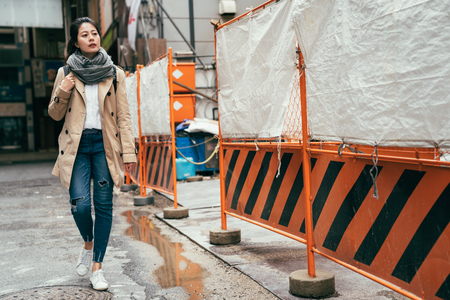 female people wearing coat walking on the street in osaka japan in spring. young girl pass through the under construction of tall building in the urban city sunny day. water on the ground after rain.