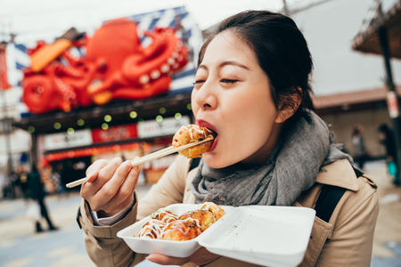 asian woman tourist trying hot takoyaki by chopsticks. young elegant lady standing in front the street vendor shop selling tacoyaki. girl eating delicious octopus balls. Stockfoto