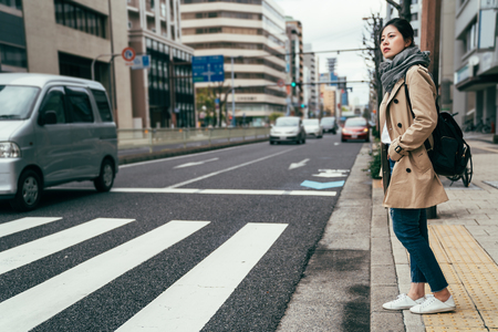 japanese people walking waiting for traffic lights to cross busy road with car driving through. Asian Chinese woman living in city in osaka. young lady standing on the street in spring wearing scarf. Archivio Fotografico - 115301826