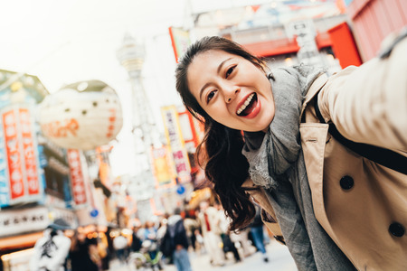 young female traveler cheerfully taking selfie on busy street in tsutenkaku osaka japan. girl smiling at the camera self portrait with peffer fish balloon floating on the sky in sunshine.