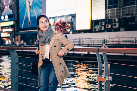 elegant office lady carry slr camera sightseeing dotonbori osaka japan in her business travel trip free time. young girl tourist standing relaxing next to the river. nippon running man advertisement.