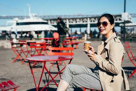 Young woman enjoying coffee sitting at the cafe outdoors near the harbour in san francisco usa. oakland bay bridge with blue sky in the background. asian lady cheerfully smiling holding cellphone.