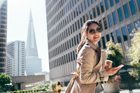 female young student standing outdoor city park with tall tower skyscraper in background. college girl smiling face camera holding coffee cup and mobile phone after course in university.