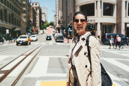 cheerful young college student wearing sunglasses smiling face camera walking on zebra crossing on sunny day. People are driving their private cars to work in san francisco. taxi transports in city. Stok Fotoğraf