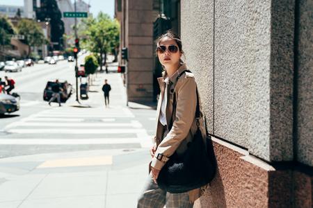 Attractive young asian woman in smart casual outfit standing on the road in san francisco under sunlight wearing sunglasses. chinese female against wall and looking into distance at her left side. 版權商用圖片