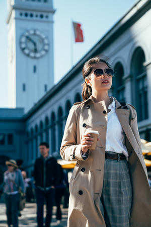 young lady traveler holding coffee cup walking sightseeing visiting in ferry building in san francisco. girl tourist in sunglasses business travel trip in america along. big tower clock in background