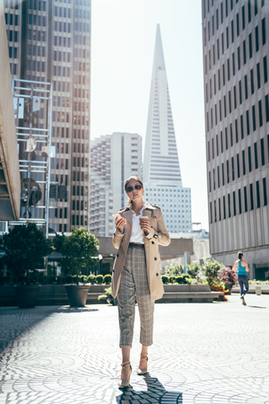 full length female office worker walking in high heels using mobile phone texting message replying email for work. young asian woman in sunglasses walking outdoor ground square of business building.