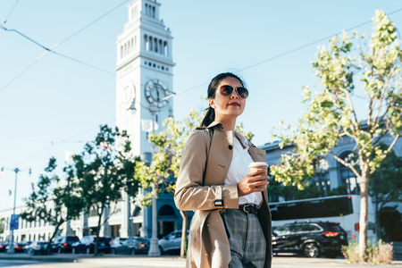 young girl in sunglasses confident enjoy relaxing walking on street with traffic jam cars in background under sunshine. asian woman holding coffee cup standing outdoor. big clock tower ferry building Stok Fotoğraf