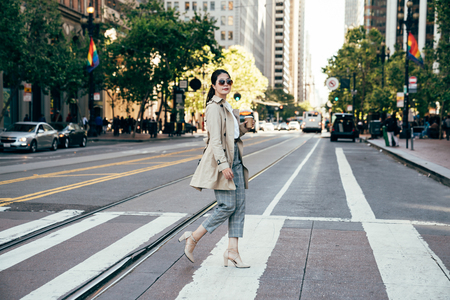 rainbow flag hanging on street in background in san francisco city urban. young college girl holding coffee cup going to university walking on zebra crossing. asian woman in sunglasses in summer. Stock Photo