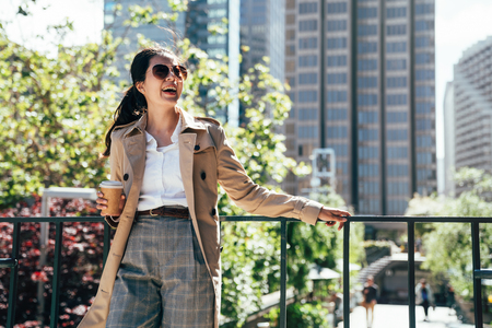 asian businesswoman drinking coffee while a short break outdoor relying against handrail. sky garden in company busy city. young girl in sunglasses cheerfully smiling resting on sunny day.